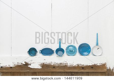 Old blue and turquoise metal pots on white shabby chic wooden background for kitchen decoration.