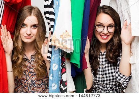 Young beautiful women at the weekly cloth market - Best friends sharing free time having fun and shopping in the old town in a sunny day - Girlfriends enjoying everyday life moments.