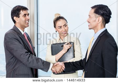 Asian secretary introduces applicant to boss for job interview and they shake hands in office