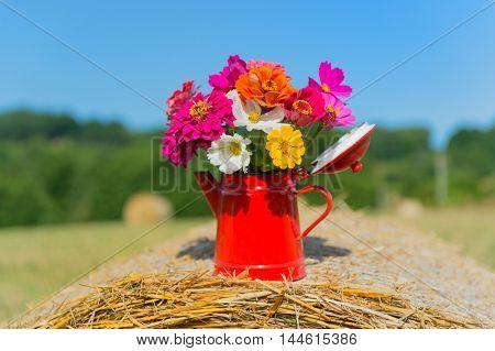 Bouquet garden flowers on hay roll in summertime