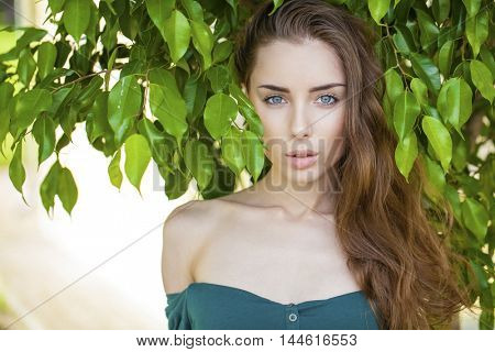 Portrait of a beautiful young woman on a background of green leaves, summer outdoors