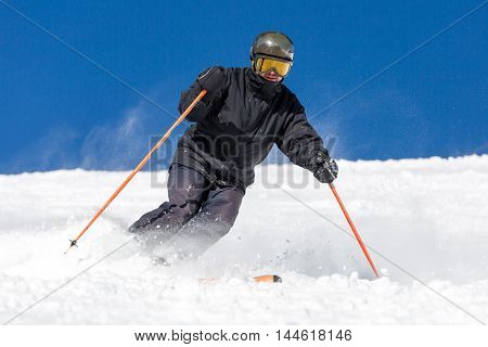 Male skier skiing in fresh snow on ski on a sunny winter day at the ski resort Soelden in Austria.