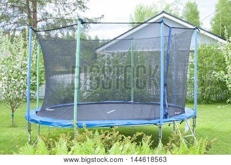 Blue Trampoline On The Lawn In Garden
