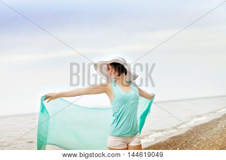 Portrait of a beautiful woman with a turquoise scarf and a big white hat on the beach enjoying the summer. Jumping on the beach. Travel End vacation. The concept of freedom.
