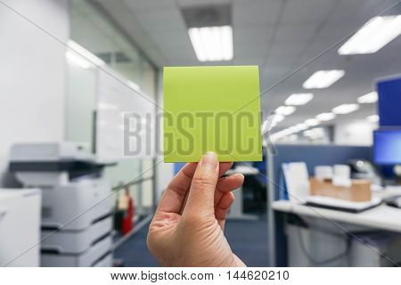 hold a green postit in hand with office background