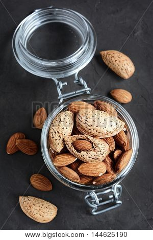 Assorty of nuts: almonds and hazelnuts in a glass jar poster