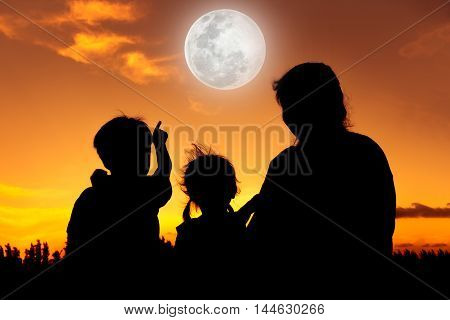 Silhouette back view of family sitting and relaxing together. Boy point to full moon on gold sky background. Happy family spending time together.