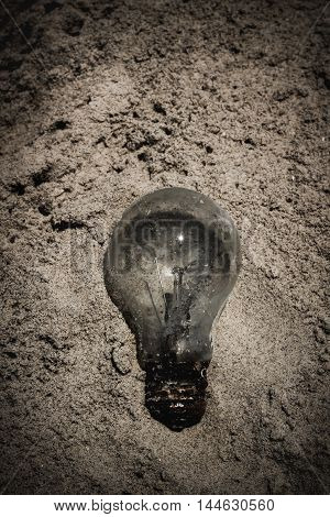 Light bulb was throw away on the beach. Environmental pollution concept picture. Vignette and vintage tone effect. Low key style.