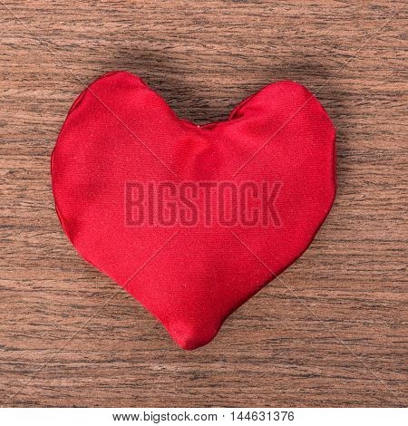 one red homemade sewn heart on wooden background concept Valentine's day greeting card close up
