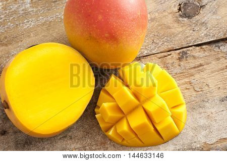 Fresh ripe tropical mango whole and sliced through to show the juicy flesh with a one section cut into a decorative hedgehog pattern overhead on rustic wood
