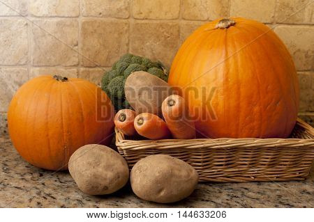Selection of fresh raw whole vegetables in a basket with pumpkin squash potato carrots and broccoli in a vegetarian still life on rustic wood