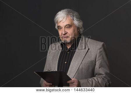 Portrait of handsome professor man in business suit holding clipboard. Demanding teacher of university or colleage looking at camera in studio.