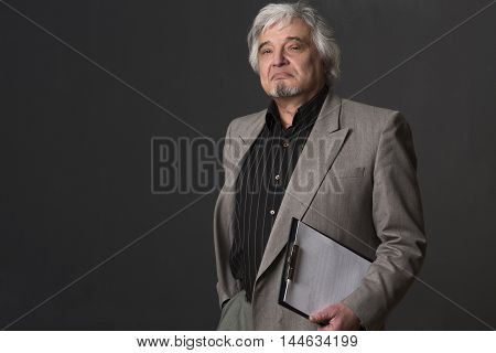 Portrait of serious professor man looking at camera isolated on black background. Handsome teacher of university or colleage in studio.
