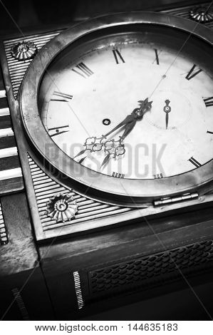 Vintage grandfather clock decorative wooden body and white dial fragment. Close up black and white stylized photo