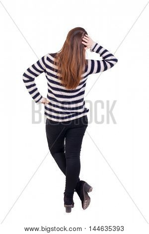 back view of standing young beautiful woman. Girl in a striped jacket thoughtfully scratching his head.