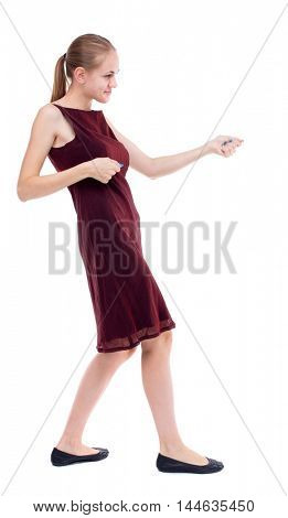 back view of standing girl pulling a rope from the top or cling to something. Isolated over white background. A girl in a burgundy holds the rope.