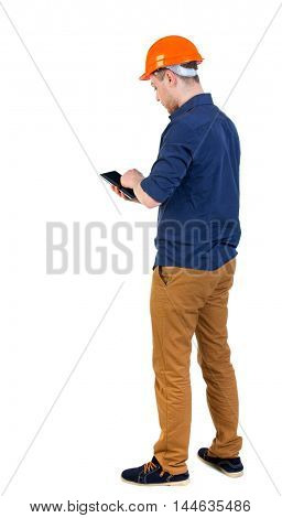 Backview of business man in construction helmet stands and enjoys tablet or using a mobile phone. Isolated over white background. a man in a blue shirt and hat working on a tablet.