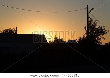 the outlines of the houses durins sunset