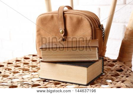 Books with handbag on wicket chair