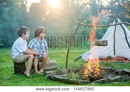 Two Sweet Children, Boy Brothers, Camping Outside Summertime On Sunset