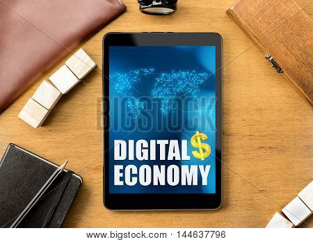 Digital Economy Word On Tablet With Clock ,box,notebook,leather Bag, Pencil And Mouse On Wooden Tabl