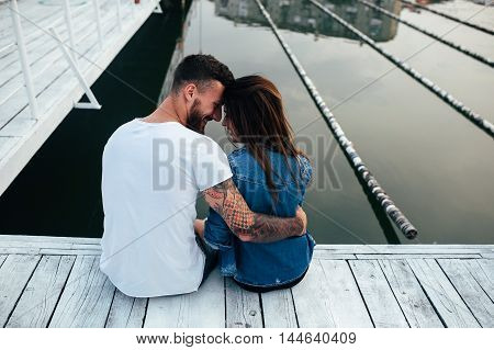 beautiful couple posing on a wooden pier at lake