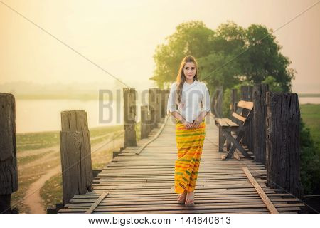 Beautiful girl in Mamdalay Myanmar traditional costume Burmese woman holding traditional red umbrella and walking on U-Bein Bridge