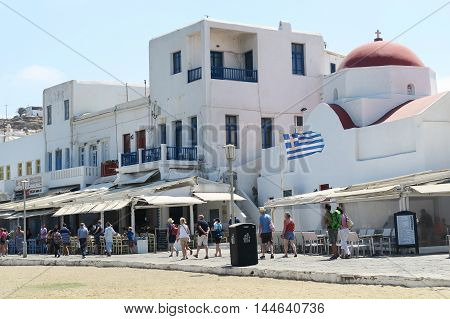 Mykonos, Greece - August 13 2016: Tourists at the Town's coastline. Mykonos has about 10.000 permanent inhabitants, most of them living in Mykonos Town (Chora).
