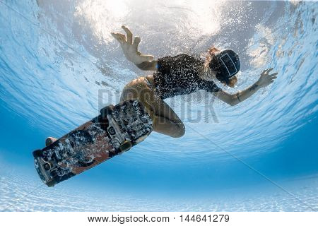 Woman skateboarding underwater in the swimming pool
