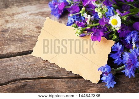 Card with bluettes, delphinium and camomile on wooden background