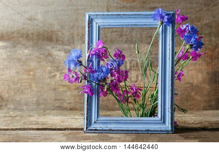 Retro frame with delphinium and bluettes on wooden background