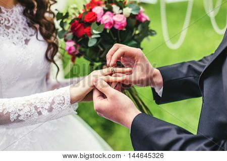 wonderful stylish rich happy bride and groom puts wedding ring at a wedding ceremony in green garden near white arch