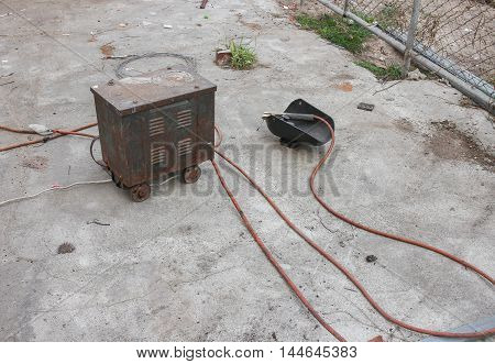 Welding and mask still life equipment  of rod-holder with cable and electrode for electric arc on a cement floor.