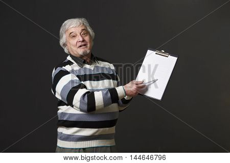 Handsome mature professor man of university or colleage holding clipboard and pen when explaining new theory, concept ot prove in studio.