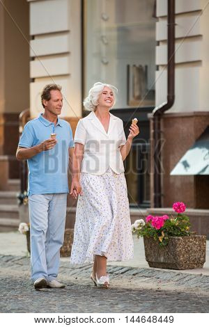 Couple is walking and smiling. Mature people with ice cream. Romantic time spent together. Feel the mood of summer.
