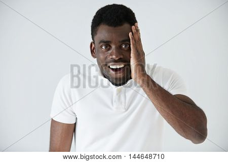 Portrait Of Excited Shocked African American Male Looking In Full Disbelief, Hand On Cheek, Mouth Wi