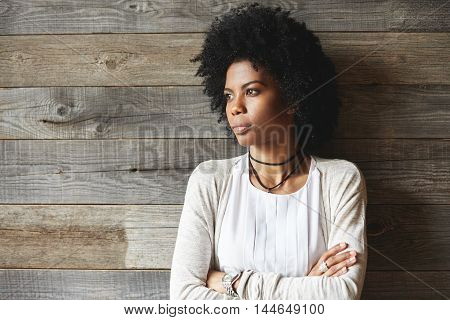 Attractive African American Woman With Afro Hairstyle Standing With Folded Arms Against Wooden Wall