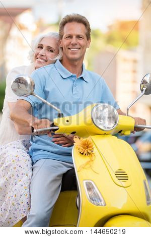 Man and woman are smiling. Mature couple on yellow scooter. Keen on tourism. Keep active lifestyle.