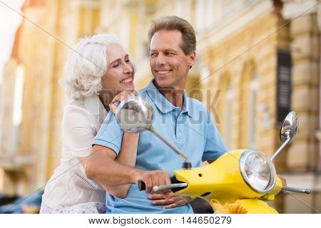 Lady hugs man on scooter. Couple looking at each other. Time that you won't forget. Love is priceless.