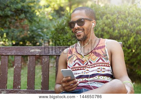 Handsome Young African Bearded Man Wearing Stylish Shades And Tank Top Relaxing In Shadow On Bench I