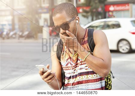 Handsome African Man Wearing Stylish Sunglasses, Looking At His Mobile Phone In Shock, Surpised With