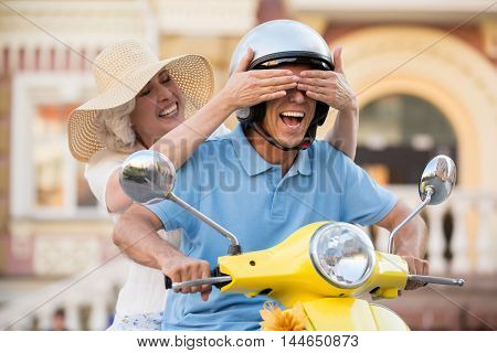 Woman closes man's eyes. Smiling mature couple on scooter. Jokes on the road. Guess where we are.