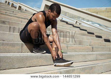Muscular Dark-skinned Male Athlete In Black Sportswear Holding His Injured Leg With Both Hands, Mass