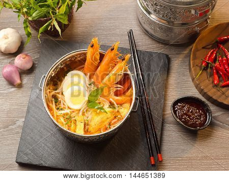 Shrimp soup with laksa egg sprout onion garlic chili sauce and noodle on wooden tray