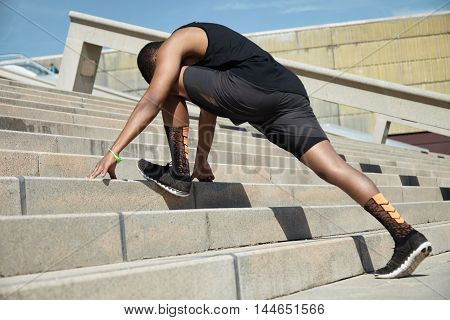Young African Jogger With Fit Athletic Body Wearing Black Running Shoes And Outfit Doing Stretching