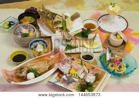 Spring Banquet Kaiseki seafood meal with braised and steamed snapper fish dimsum wasabi sushi dumplings and soyal sauce on the table