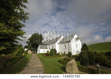 JELLING DENMARK - AUGUST 22 2016: Jelling church and Harald Bluetooths big Rune Stone - The Jelling Monuments are a UNESCO World Heritage Site. August 22 2016