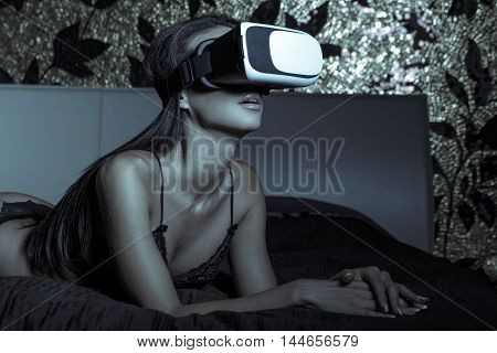 Sexy woman in underwear using VR glass in bed in dark virtual reality