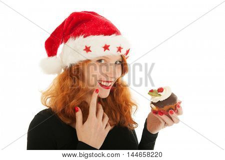 Young red haired Christmas girl eating cake with cream
