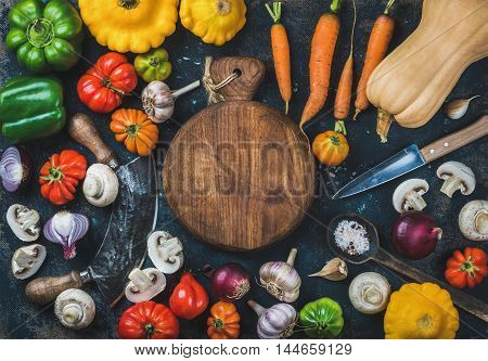 Tomatoes, onions, mushrooms, carrots, pumpkin, patissons, garlic, spices and knives on dark blue grunge plywood background with wooden round board in center. Top view, copy space